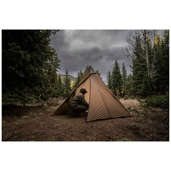 Kifaru International Sawtooth - Tent-Shelter with a Person Inside in the Middle of the Woods
