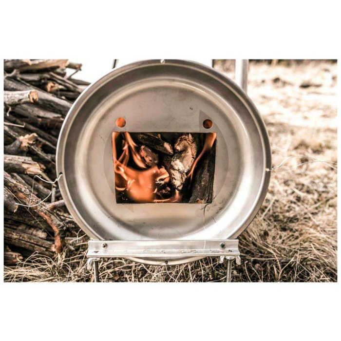 Kifaru International Smith Cylinder Stove photo of Cylinder with burning food inside and more wood to the side