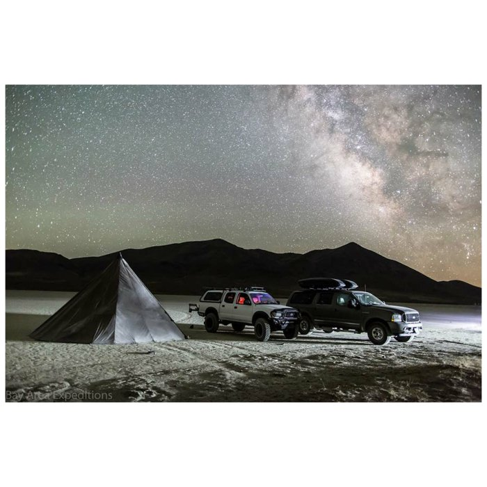 8 Man Tipi at night with stars in the sky visible and two trucks with tent next to them on dessert