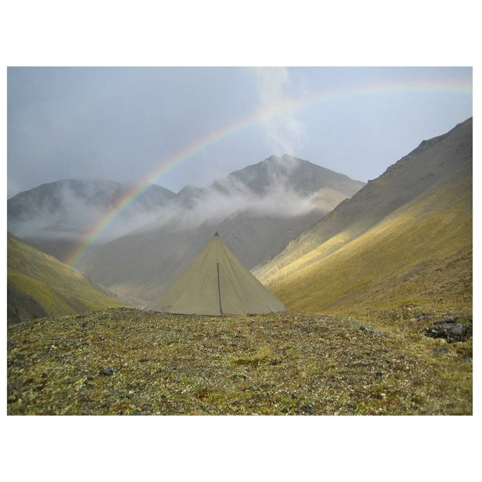 8 Man Tipi during the day in the middle of the mountain with no forestation and a rainbow visible