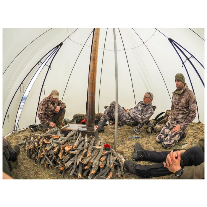 8 Man Tipi with 4 People Having a Relaxing Time in the Tent and with enough wood wide angle photo