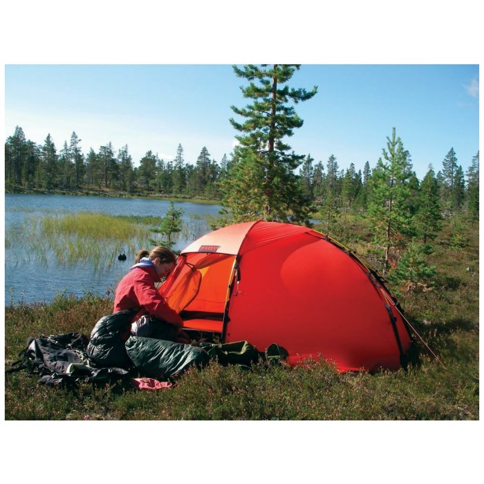 Hilleberg Soulo Sand Red Tent in Sweden with a Woman Outside Setting Up with Green Areas Visible