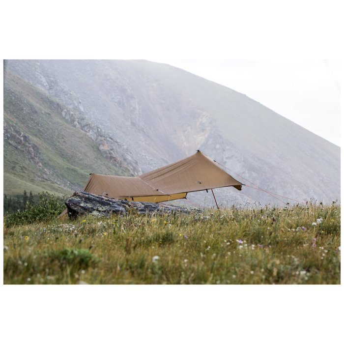SuperTarp side photo with mountains visible in the background and a beatufiul peaceful field